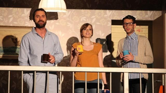 Kandlbauer im Pyjama mit zwei weiteren Hauptdarstellern auf der Bühne.
