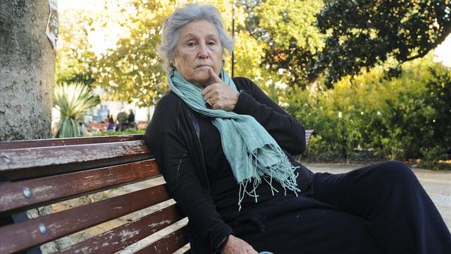 Die Schriftstellerin Wassyla Tamzaly sitzt auf einer Parkbank.