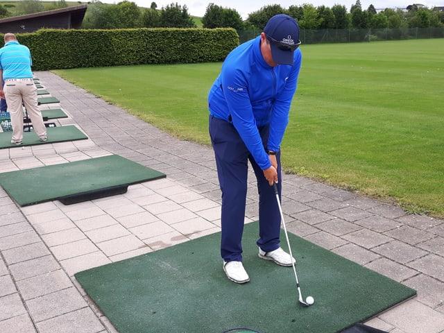 Golflehrer steht auf Kunstrasen und zeigt die richtige Haltung beim Abschlag.