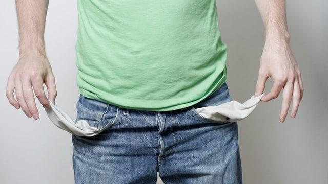 Mann zeigt seine leeren Hosentaschen