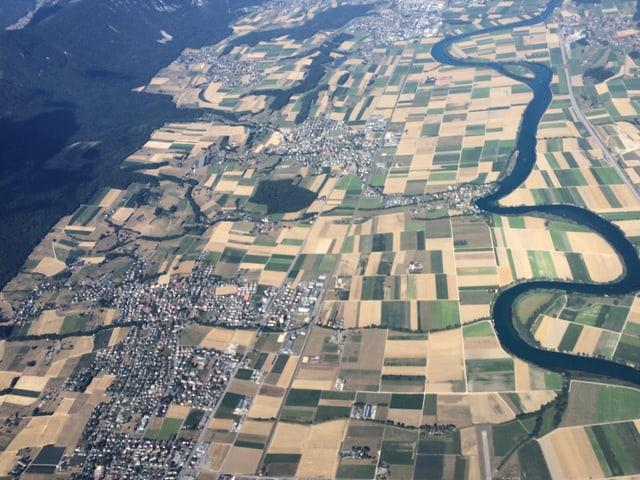 Luftbild auf Landschaft mit hellbraunen Felder und einem Fluss.