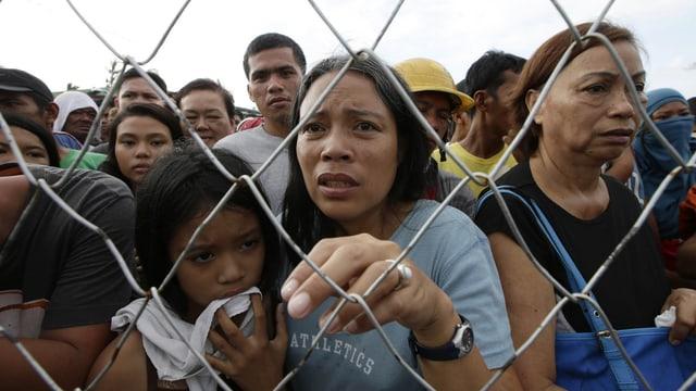Menschen warten am Flughafen auf Hilfe hinter einem Zaun.