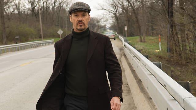 Ein Mann mit einem Beret geht auf einer Strasse. Im Hintergrund ist ein Auto zu sehen.