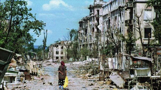 Ein Frau geht allein eine von Ruinen gesäumte Strasse entlang
