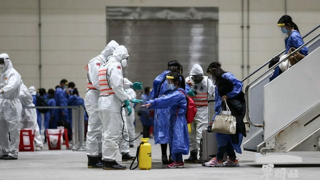 Am Flughafen führen Menschen in Schutzanzügen Coronatests bei Ankömmlingen durch.