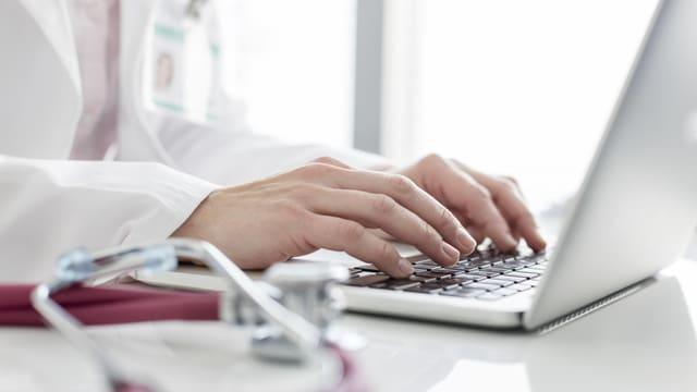 Eine Ärztin schreibt etwas in einen Laptop.