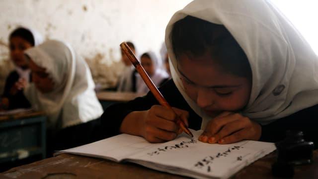 mattatscha che scriva en ses carnet en ina scola en l'Afganistan