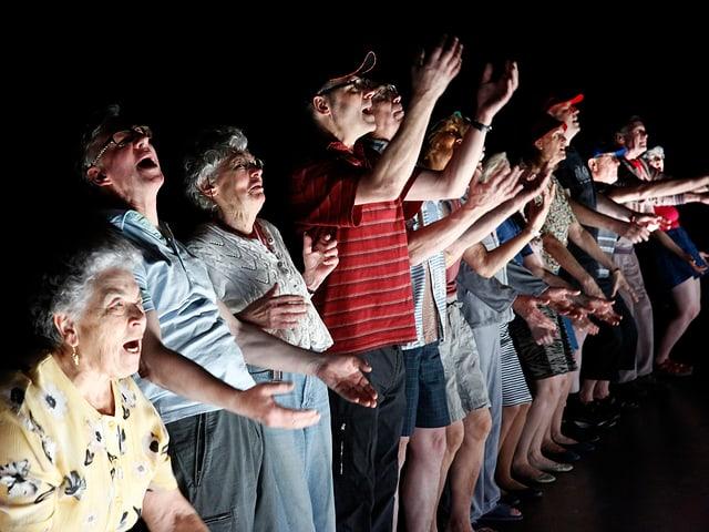 Eine Gruppe älterer Menschen steht in der Reihe und schwingt die Arme durch die Luft.