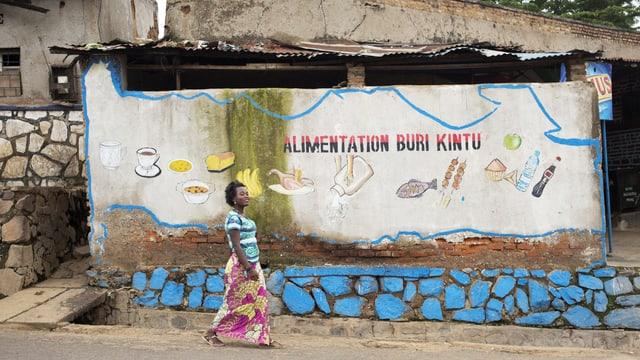 Eine Frau läuft an einer Wand vorbei, auf der mit aufgemalten Lebensmitteln geworben wird.
