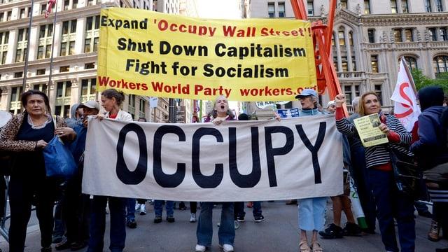 Occupy Wall Street Demonstration mit transparenttragenden Frauen im Vordergrund