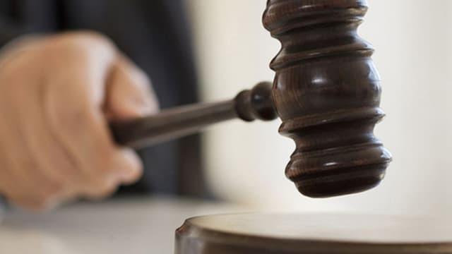 Ein Richter schlägt mit dem Hammer auf ein Brett.