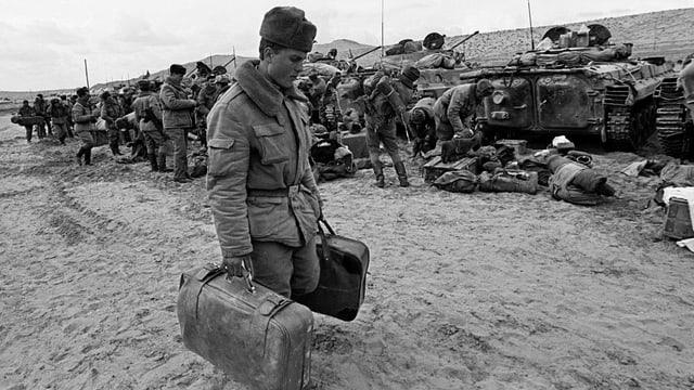 Ein russischer Soldat trägt seine Koffer. Im Hintergrund sind Panzer zu sehen.