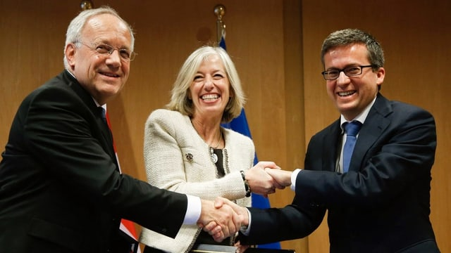 Zwei Herren und eine Dame schütteln Hände und halten ein Dokument