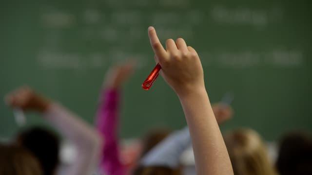 Ein Kind streckt die Hand in die Höhe.