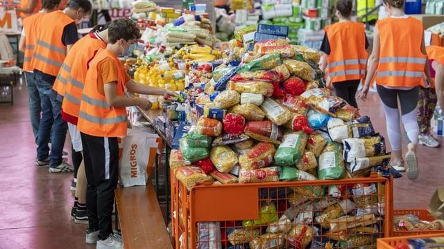 Menschen mit Leuchtweste und Gesichtsmaske beladen Papiersäcke mit Lebensmitteln.