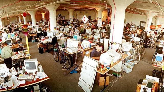 Grossraumbüro, auf allen Tischen stehen Comupter. Es herrscht kreatives Chaos (neben vielen Tischen stehen Fahrräder).