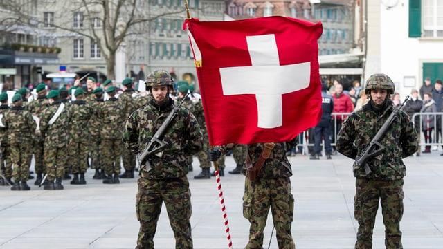 Soldaten stehen auf einem Platz. Einer hälte eine Schweizerfahne vor dem Gesicht.