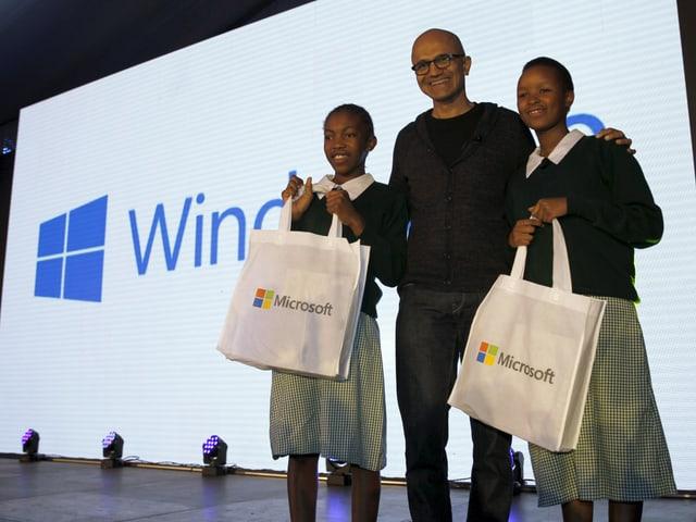 Satya Nadella auf einer Bühne zusammen mit zwei Schülerinnen.
