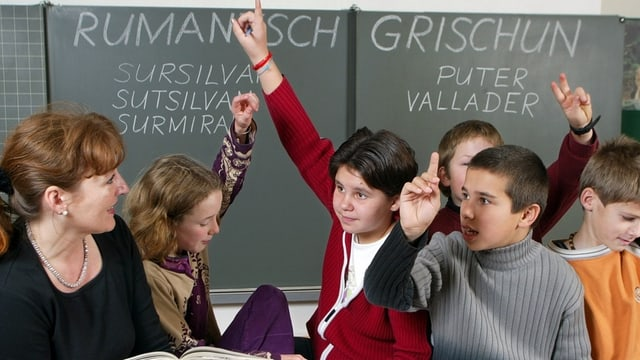 Eine Lehrerin und ihre Schüler im Klassenzimmer.