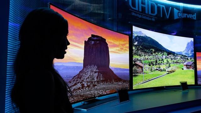 Silhouette einer Frau die zwei HD-Bildschirme betrachtet.