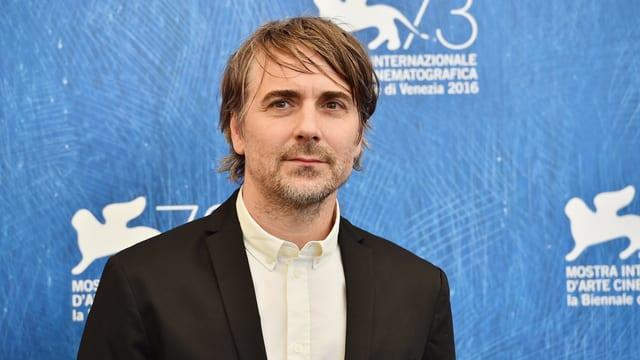 Ein Mann mit braunen Haaren in Hemd und Anzug.