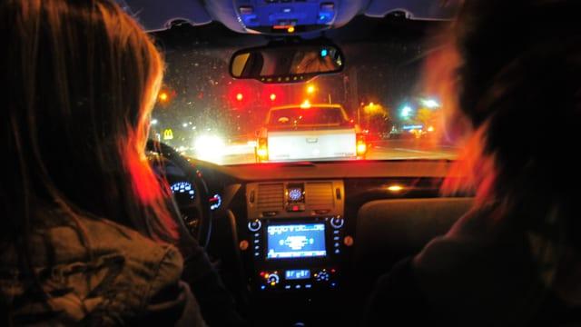 Zwei Frauen blicken im Dunkeln durch die Autoscheibe auf die dunkle Strasse.