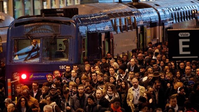 Pendler steigen aus dem Zug auf völlig überfülltes Peron.