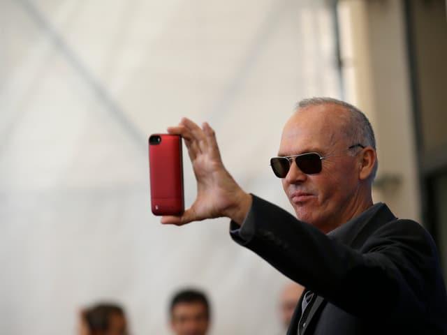 Schauspieler Michael Keaton fotografiert mit dem Handy.
