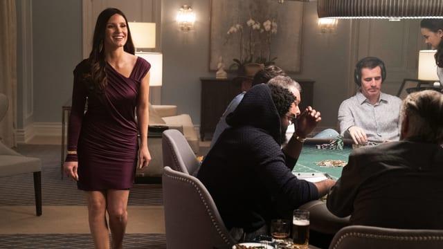 Frau in Abendkleid läuft entlang eines Pokertisches.