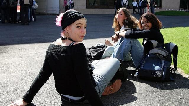 Schülerinnen sitzen auf einem Pausenplatz auf dem Boden