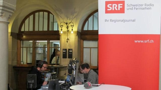 Zwei Männer sitzen vis à vis vor ihren Computern, davor ein Tisch mit einem Mikrofon und ein Banner mit dem SRF Logo.
