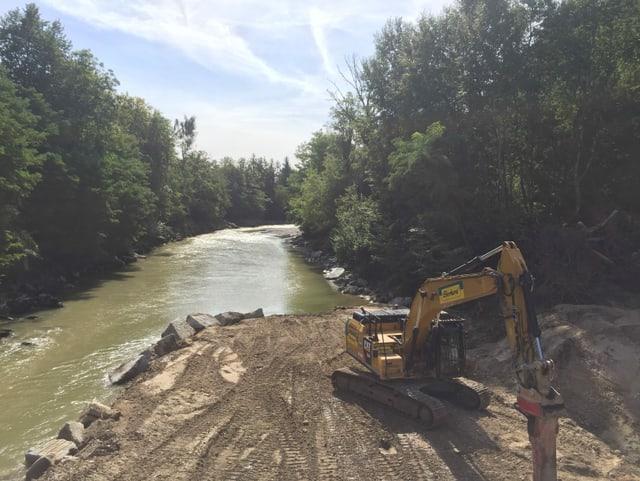 Bagger auf Aufschüttung in Fluss, rundherum Bäume.