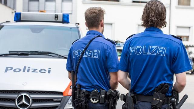 Zwei Polizisten der Luzerner Polizei stehen neben einem Einsatzfahrzeug.