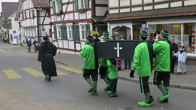 Fasnächtler im grünen Kostüm tragen einen schwarzen Sarg durch Allschwil.