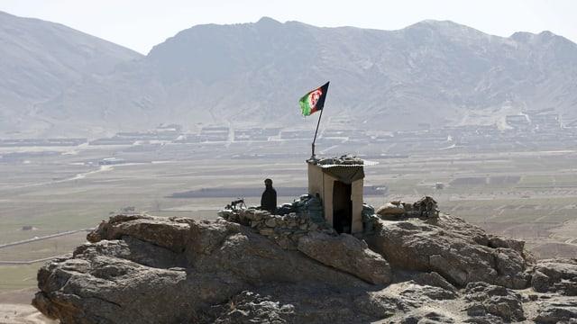 Symbolbild: Ein Aussichtsposten der afghanischen Armee über einem breiten Tal, ein Soldat blickt unter einer Afghanistan-Flagge in die Ebene.