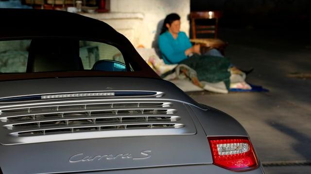 Bild eines parkierten Porsches, im Hintergrund eine Bettlerin auf dem Trottoir.