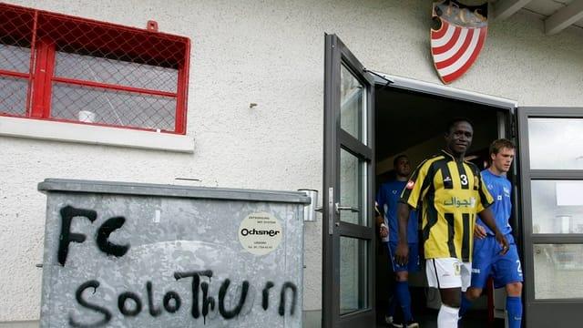 """Spieler verlassen das Kabinengebäude des FC Solothurn, im Vordergrund ein Abfallcontainer mit dem Schriftzug """"FC Solothurn"""""""
