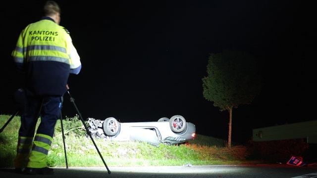 Auto liegt auf Dach neben Strasse, im Vordergrund Polizist mit Kamera