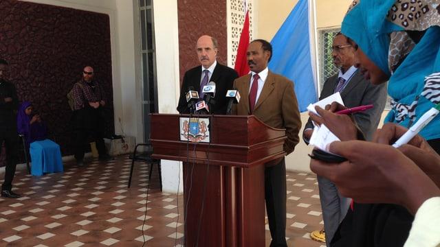 Der Botschafter und der Präsident stehen hinter einem Rednerpult.