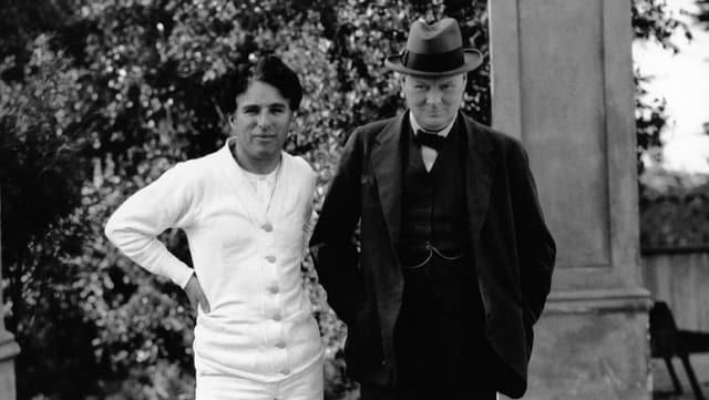 Charlie Chaplin und Winston Churchill stehen nebeneinander.