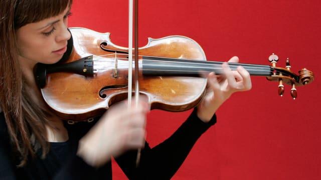 Ruth Palmer spielt Geige vor einem roten Hintergrund.