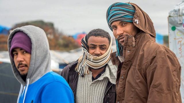 Drei junge Männer, dick eingepackt – im Hintergrund eine Zeltstadt.