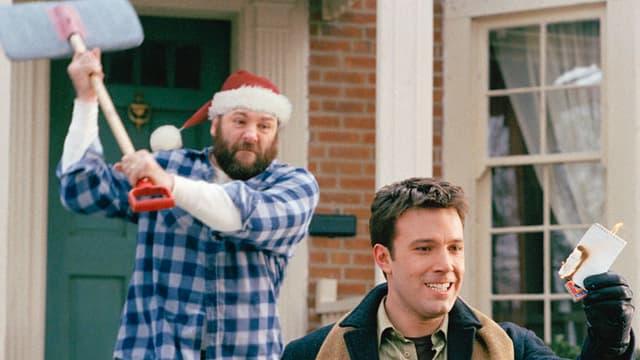 Ein Mann mit Nikolaus-Mütze holt mit einer Schaufel aus und zielt von hinten auf den Kopf eines anderen Mannes.