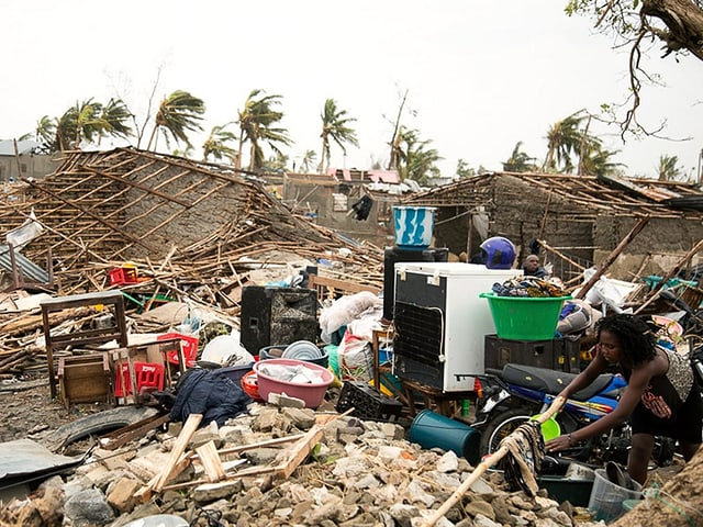 Zerstörte Häuser, eine Frau versucht, Wäsche zu waschen.