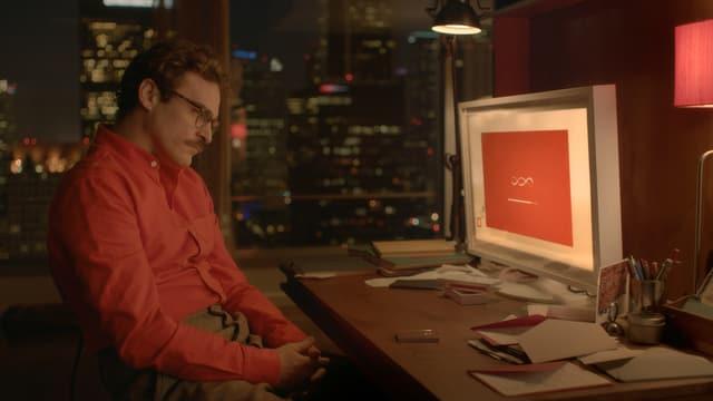 Joaquin Phoenix sitzt im FIlm «Her» vor einem Computer und wartet.