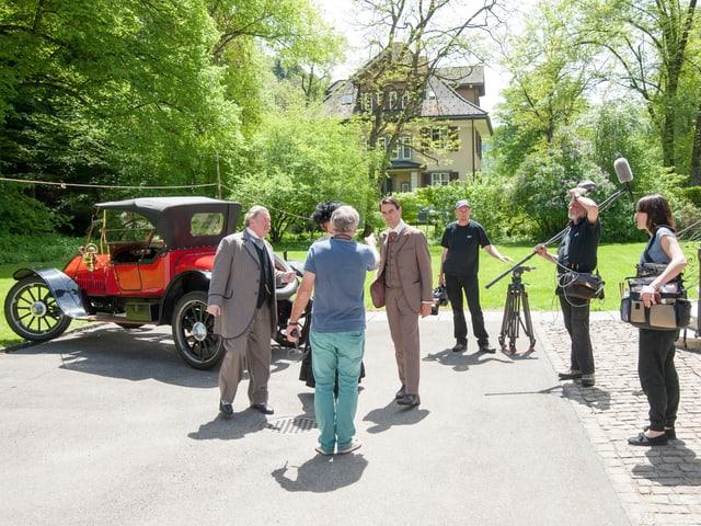 Fernsehteam und zwei Schauspieler draussen vor Villa, im Hintergrund Garland