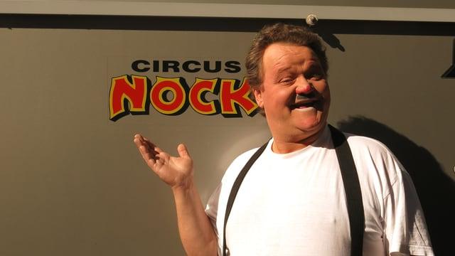 Clown Roli Noirjean steht geschminkt vor einem Circuswagen. Auf dem Wagen ist der Schriftzug Circus Nock zu lesen.