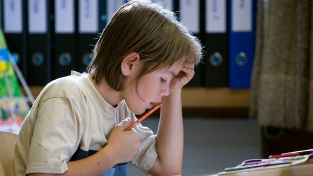 Scolar che scriva in clausura da matematica en la scola da Monstein a Tavau.
