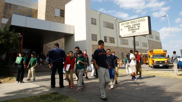 Scolars davant ina scola media en l'America.
