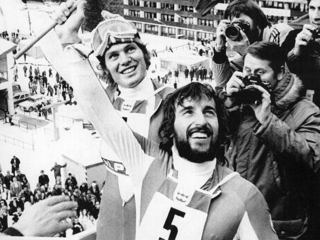 Schwarz-Weiss-Fotografie mit zwei strahlenden Skirennfahrern.